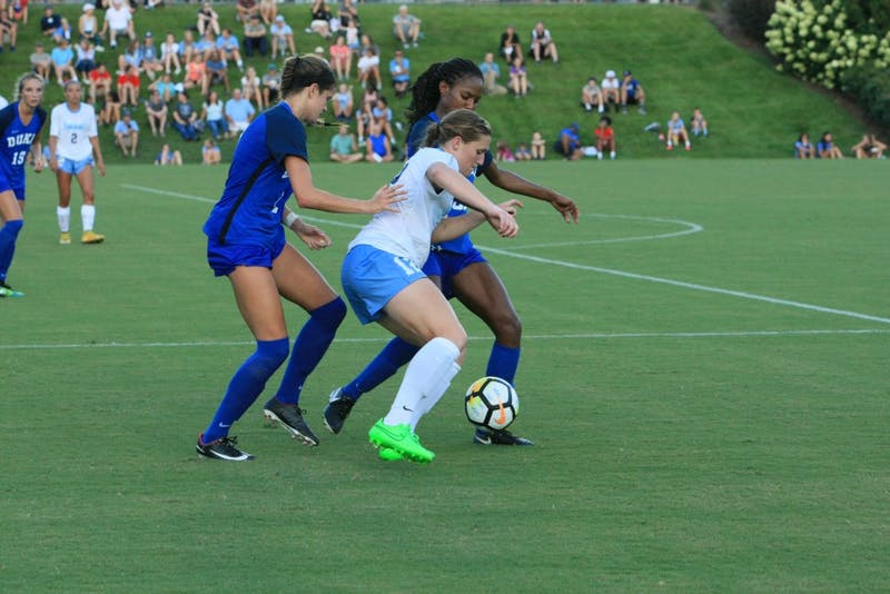 Jessie Scarpa (12) defends the ball against Duke players on Friday at WakeMed Soccer Park in Cary, N.C.