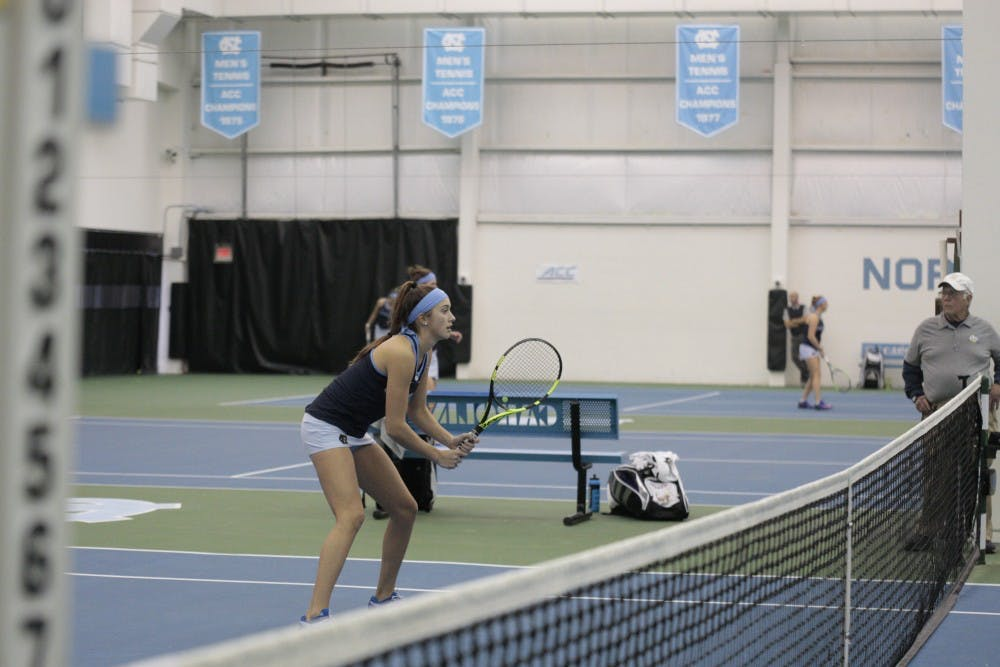 <p>First-year Cameron Morra prepares to receive a serve during a doubles match against East Carolina University at the Cone-Kenfield Tennis Center in Chapel Hill, NC on Wednesday, Jan. 23, 2019. Morra and her partner, Makenna Jones, won both sets in the match.&nbsp;</p>