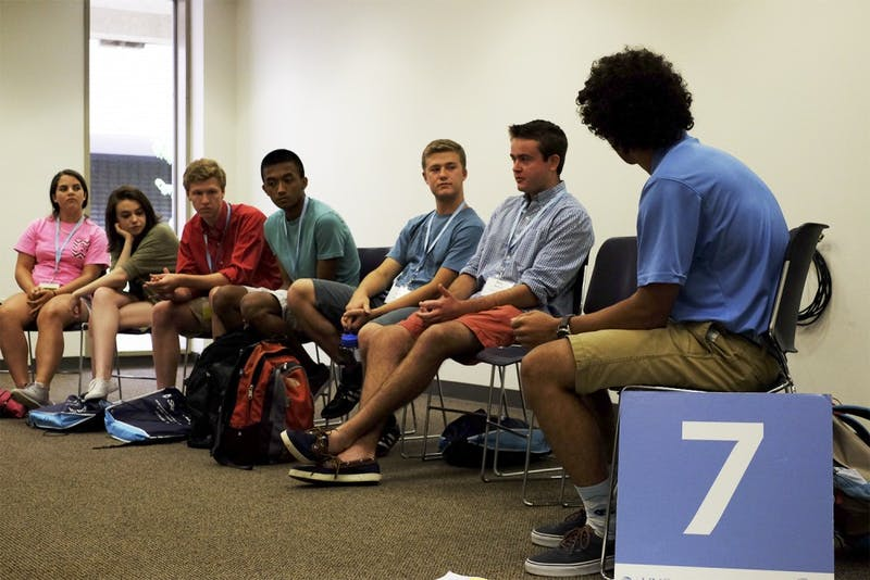 Parker Martin, an orientation leader, leads a discussion after a presentation on Monday.