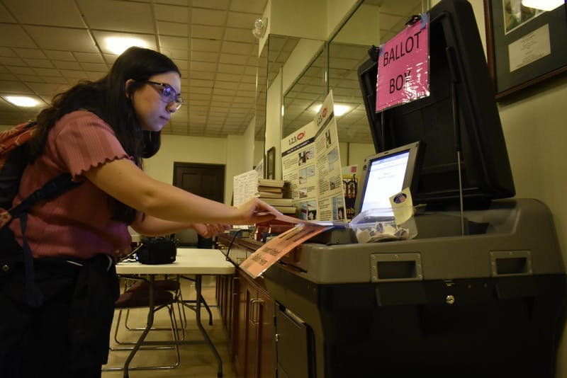 Media and Journalism student Mitra Norowzi submits her ballot at the Chapel of the Cross church at 304 E. Franklin St. on Oct. 23, 2018. The Chapel of the Cross serves as an early voter location close to the University of North Carolina at Chapel Hill's campus.