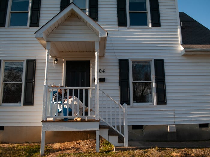 A resident of the Northside neighborhood reclines on their porch on Feb. 8, 2021. Chapel Hill's affordable housing plan continues to focus on Emergency Housing, public housing communities, and rehabilitation projects during the COVID-19 pandemic.