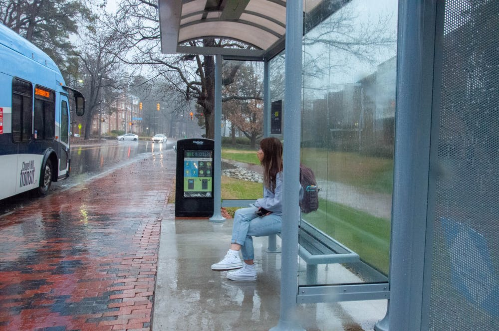 <p>A student waits for the bus at the new South Road bus stop on February 11, 2021. Chapel Hill Transit recently installed new stops and coverings for their buses.</p>