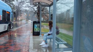 A student waits for the bus at the new South Road bus stop on February 11, 2021. Chapel Hill Transit recently installed new stops and coverings for their buses.