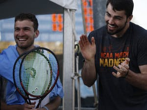 UNC men's tennis junior William Blumberg and men's basketball senior Luke Maye share a happy moment after Blumberg won both his sets against N.C. State on April 3, 2019. UNC beat the Wolfpack, 4-0.