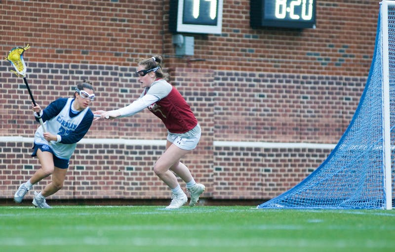 UNC senior midfielder Marisa Divietro (27) charges past Elon freshman defender Hannah Mccarthy (7) to attempt a shot on goal. The Tar Heels would start off the season with a 20-3 victory over Elon during the exhibition match on Feb. 1, 2020, at Dorrance Field.