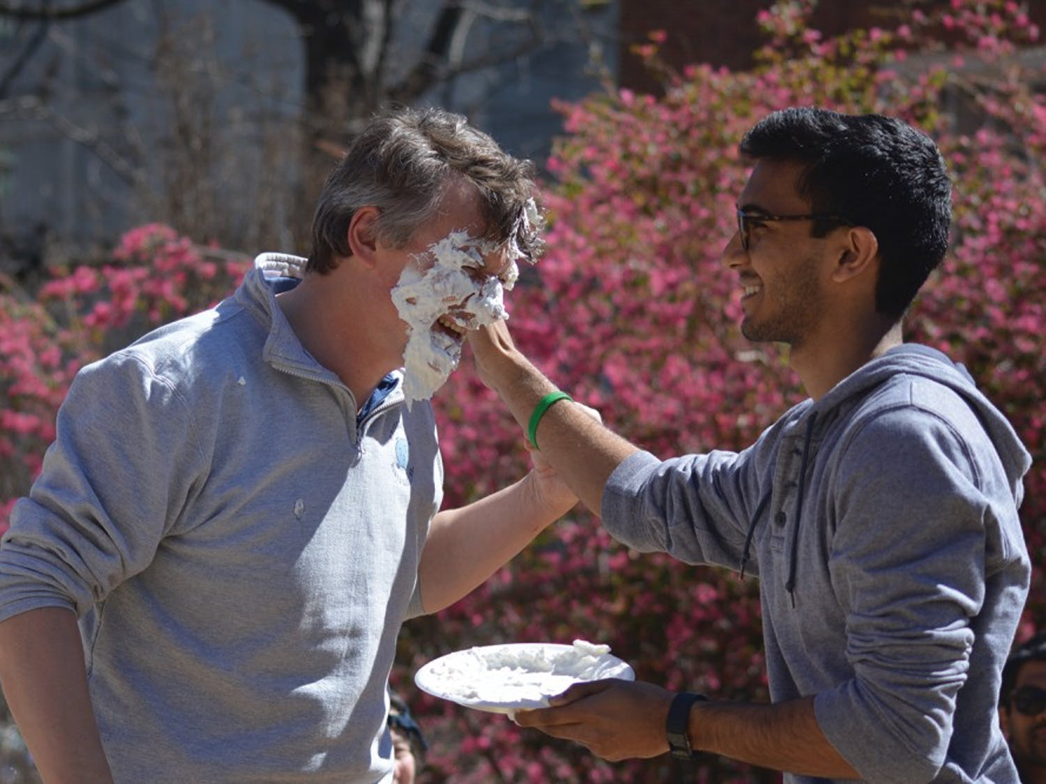 Jan-Michael Frahm (left) gets hit with a pie thrown by Sanjeev Prasada at a Pi Your Professor computer science fundraiser Wednesday afternoon.