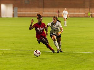 UNC junior midfielder Emily Fox (11) tries to outpace NC State freshman forward Jameese Joseph (15) in the UNC Soccer and Lacrosse Stadium on Thursday, Sept. 26, 2019. UNC beat NC State 1-0.