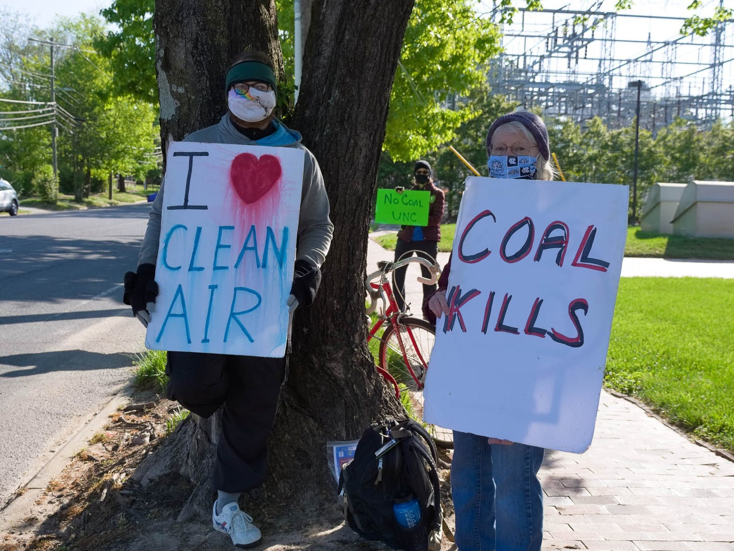 Will Zang and Margaret Lee hold up signs outside of UNC's coal plant on Friday, Apr. 23, 2021.