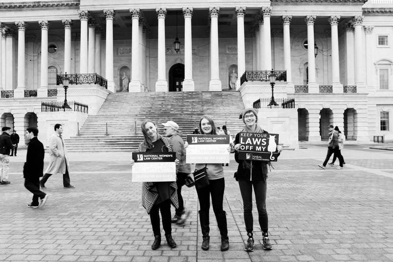 Kate Townsend, Emily Hagstrom and Amanda Witwer hold up their protest signs at the Women's March on Washington.