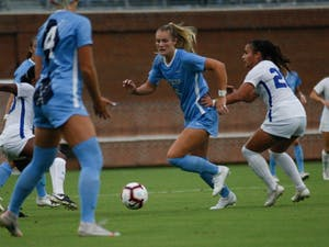UNC women's soccer defender, Taylor Otto (6), dribbles past Duke defenders during a game against Duke on August 25, 2019. UNC beat Duke 2-0.