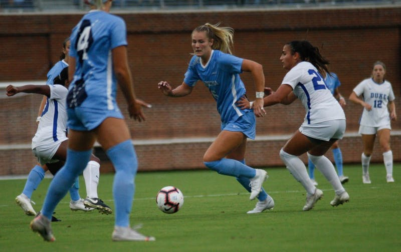 UNC women's soccer defender, Taylor Otto (6), dribbles past Duke defenders during a game against Duke on August 25, 2019. UNC beat Duke 2-0.