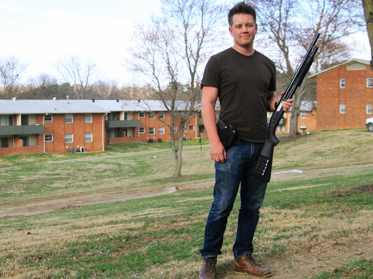 Senior mathematics major Thomas Rees holds his Mossberg 88 shotgun outside his apartment.