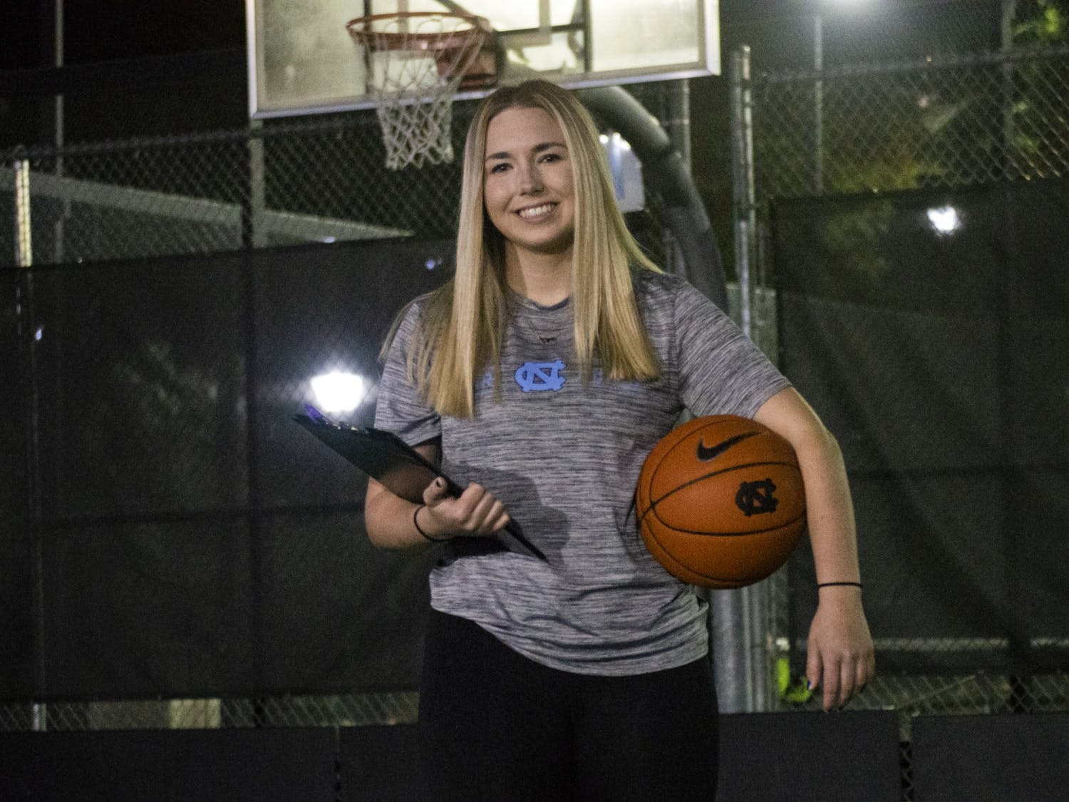 Kiersten Steinbacher, a Senior Exercise and Sport Science Major and Head Student Manager for Carolina Basketball, poses with her basketball and manager clipboard at the courts outside of Ram Village on Monday, Nov. 2, 2020.