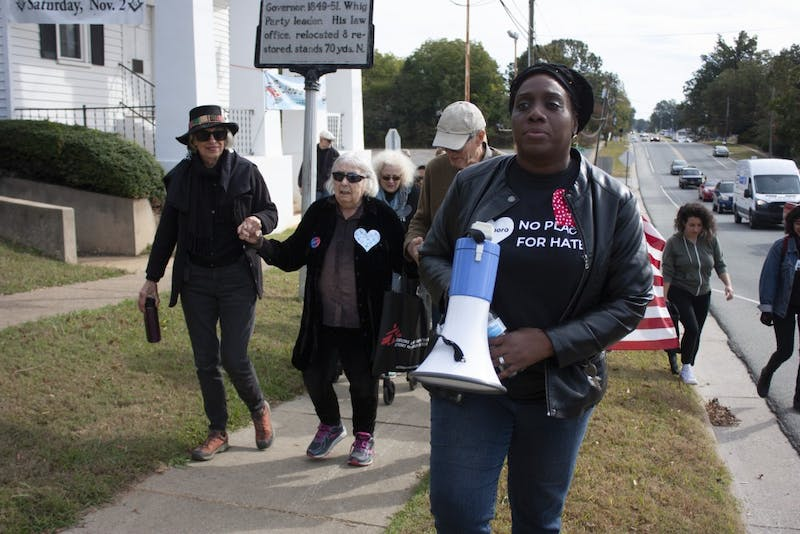 """Stephanie Terry, a Chatham resident and one of the event organizers, marches with the """"Pittsboro: No Place For Hate"""" event on Saturday, Oct. 19, 2019. """"We got to get these Confederate flags, and this racism and hate, symbols of terror in front of our middle school, down,"""" she said. """"This is a new day. It's a new time, and the symbols and vestiges of hate and racism that live in people's hearts and minds, it needs to come to an end. At the end of the day, we are all God's children, and we are one human race."""""""