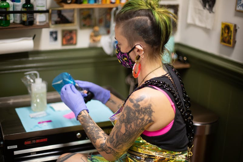 Ayden Love, a resident artist at Critter Swamp in Hillsborough, prepares to tattoo a client on Thursday, Oct. 29, 2020.