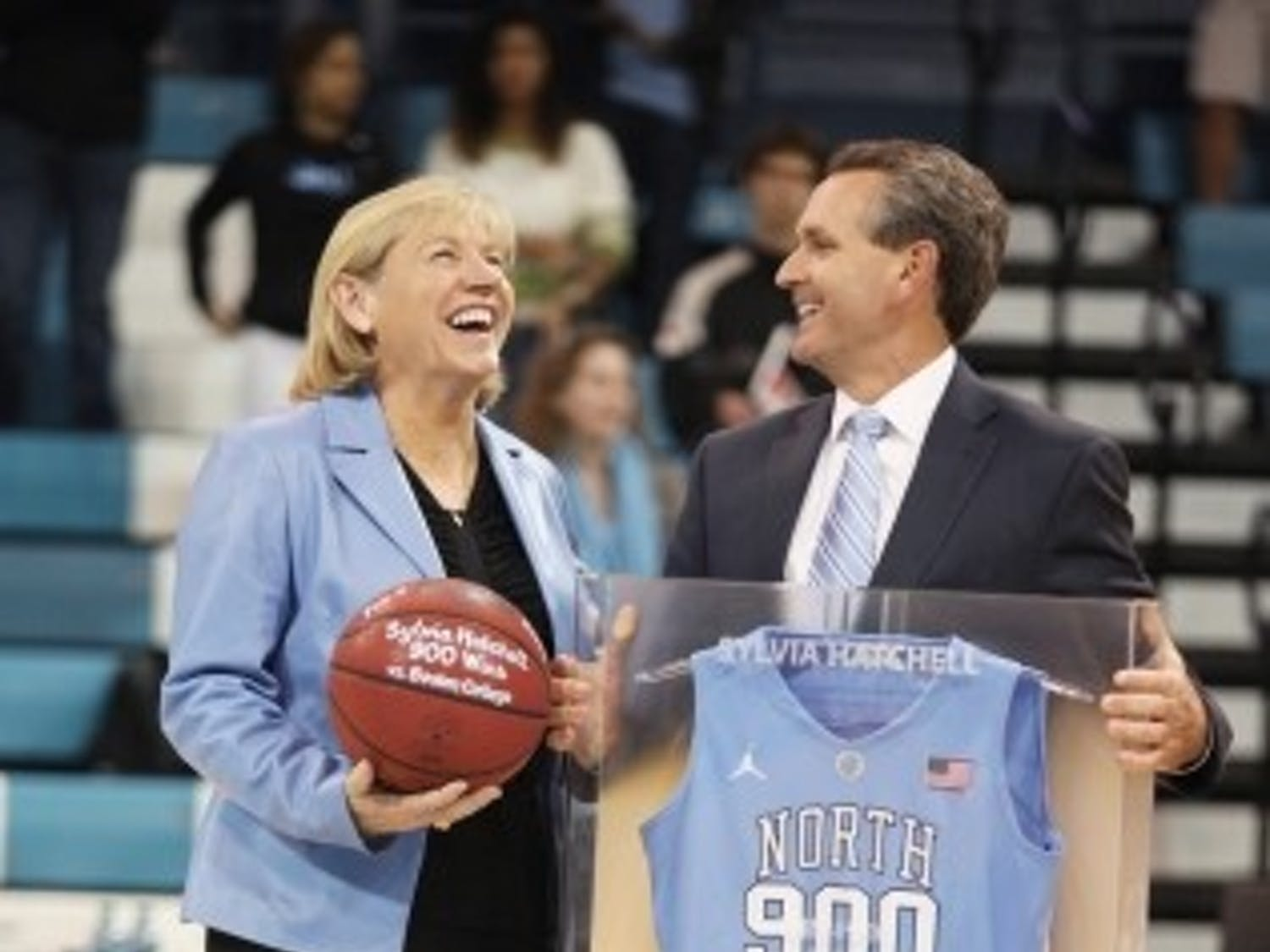 Athletic director Bubba Cunningham (right) presents women's basketball head coach Sylvia Hatchell (left) with a jersey commemorating her 900th win. The win came on Feb. 7, 2013, against Boston College in Carmichael Arena.