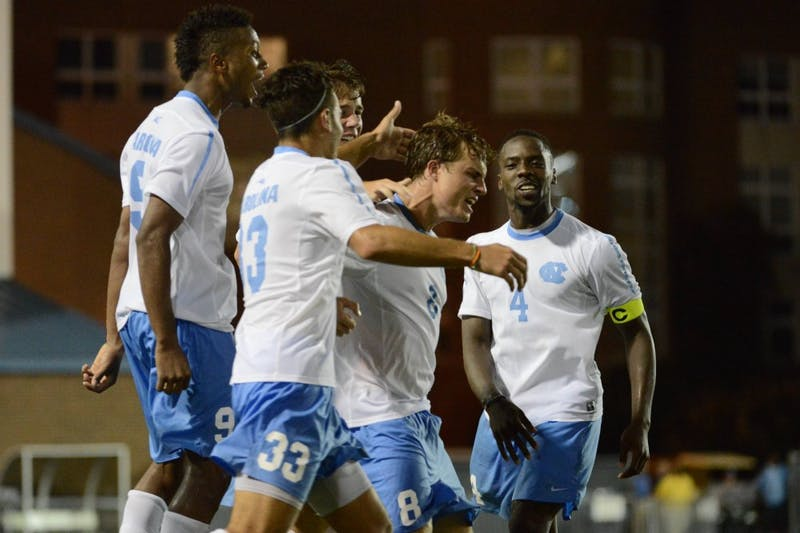 UNC forward Tyler Engel (8) celebrates with teammates after scoring the game winning goal.