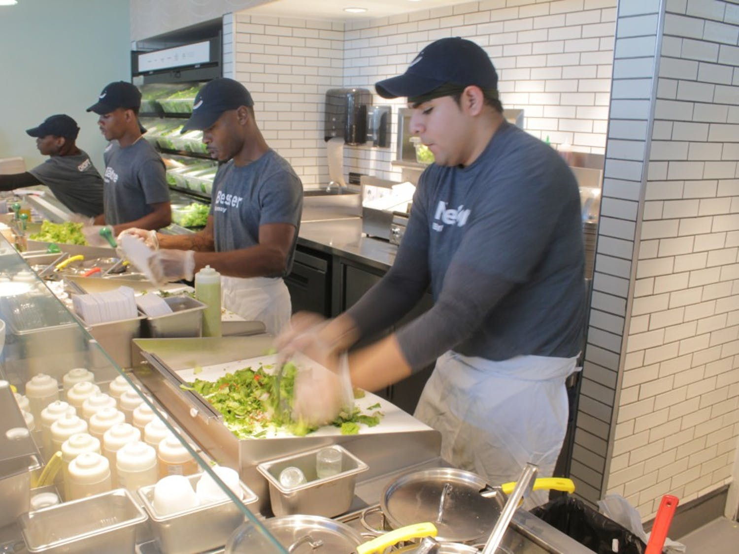 Workers prepare salad at Chopt, a new restaurant on Fordham Boulevard.