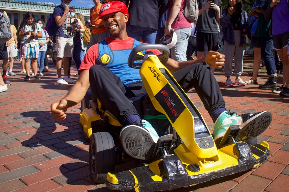 """<p>Joshua Schaffer, known virally as WeathermanJosh, dresses as Mario and rides a go-kart through the Pit on Sept. 22. """"Make sure to subscribe to my YouTube channel,"""" he prompted people as they stopped for pictures.</p>"""
