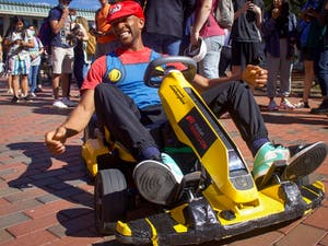 """Joshua Schaffer, known virally as WeathermanJosh, dresses as Mario and rides a go-kart through the Pit on Sept. 22. """"Make sure to subscribe to my YouTube channel,"""" he prompted people as they stopped for pictures."""