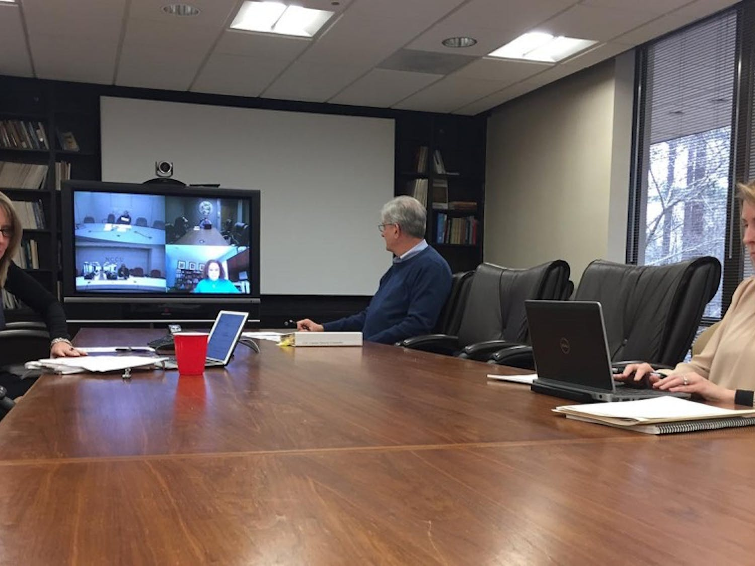 Jayne Grandes, Robert Joyce and Carrie Johnston (L-R) along with other subcommittee members discuss UNC system's policy on sexual harassment and sexual violence via teleconference. The subcommittee is part of the Board of Governor's Campus Security Committee.