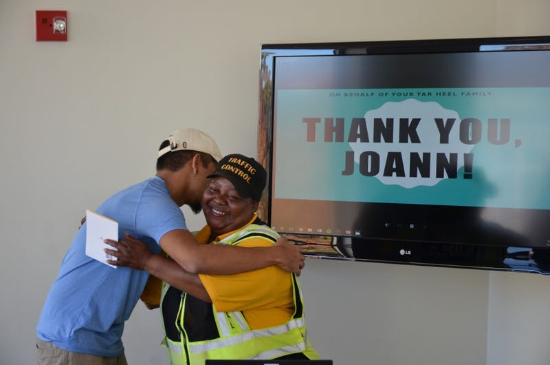Crossing guard Joann Isom hugs UNC junior Carlos Salas after receiving money raised via GoFundMe for Isom to take a trip to visit her son. Salas set up the GoFundMe fundraiser after seeing Isom's story on the Humans of UNC Facebook page.