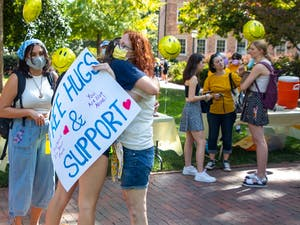Emily Midea, the mother of a first-year student, offers hugs to students behind the Old Well on Thursday. Parents and puppies filled the upper quad to offer hugs, baked goods and support as part of a parent rally organized by the Facebook group UNC-CH Parents Helping Parents.