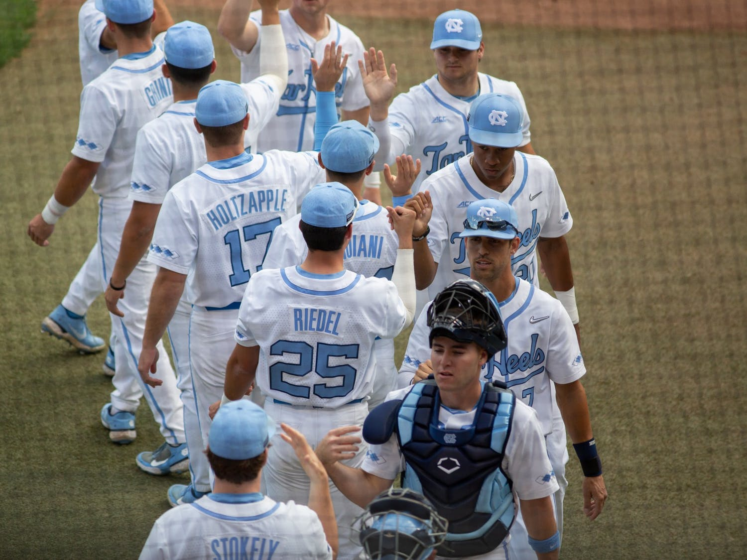 The UNC Baseball team gives each other high fives in preparation for their game against Louisville in Boshamer Stadium on Friday, May 14, 2021. The Tar Heels beat the Cardinals 5-1.