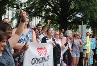 While the arrests occurred inside the building, supporters continued to rally, chant and hold up signs on Salisbury Street.