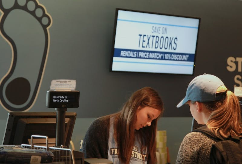 """""""Railey Pitts, a sophomore studying political science and business, helps another student with her textbooks on the lower level of UNC Student Stores. """""""