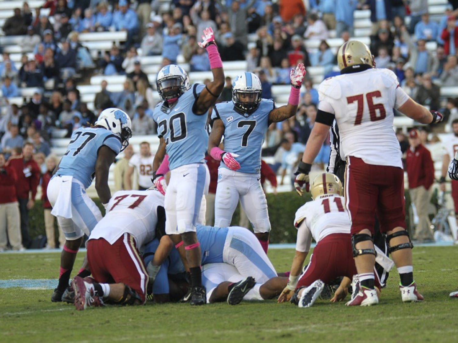 UNC's Brandon Ellerbe (20) and Tim Scott (7) motion for possession of the ball after UNC recovered the fumble.