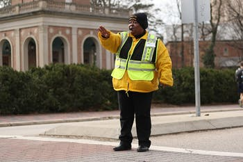 Joann Isom direct pedestrian and vehicle traffic every morning in front of the bell tower to help students get safely to and from class.