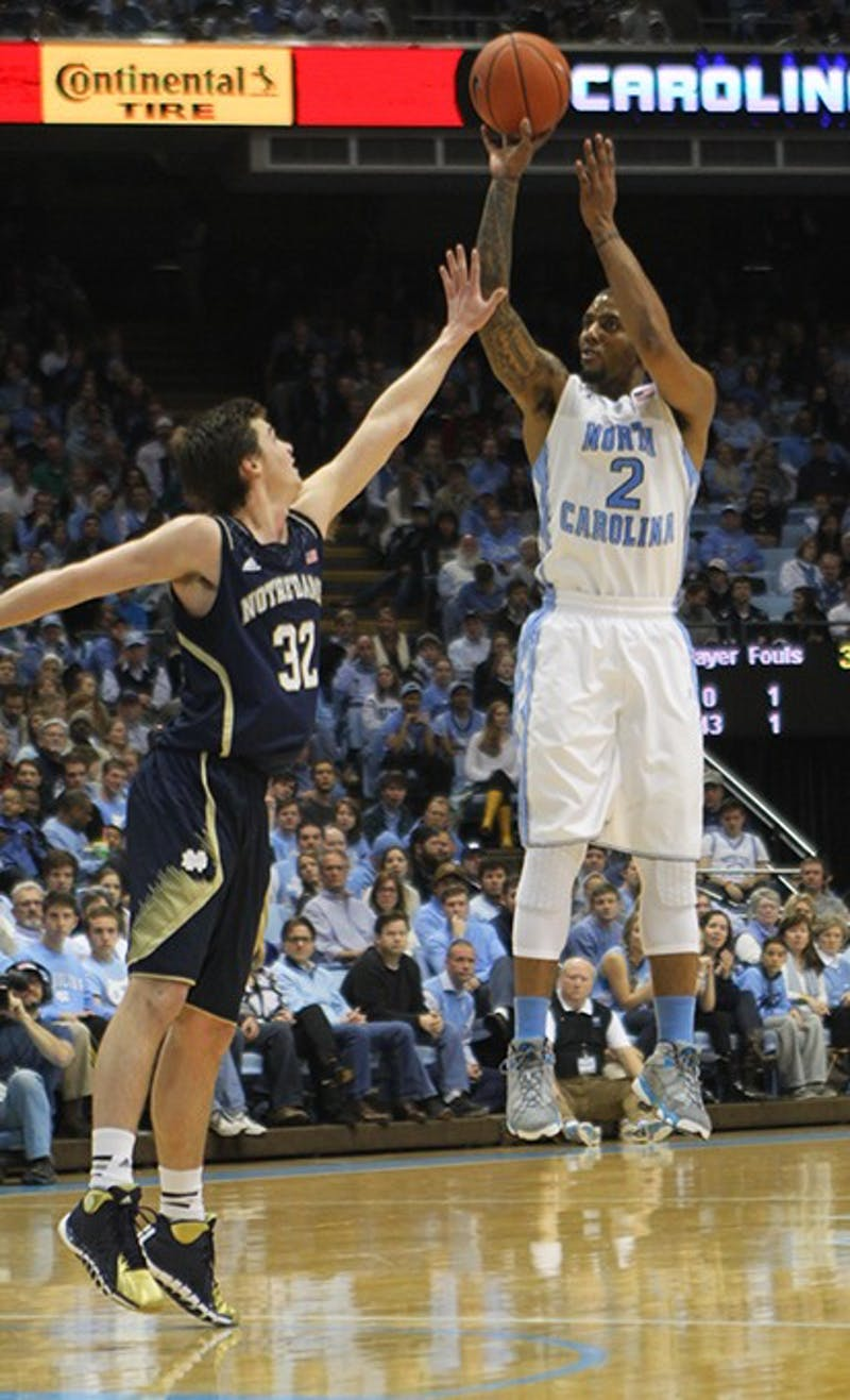 Senior Leslie McDonald (2) makes a layup as Notre Dame's Steve Vasturia (32) defends. The Tar Heels beat the Fighting Irish 63-61 Monday.