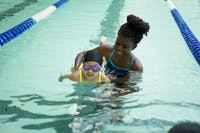 Chapel Hill volunteer, Kennedy Parkins, helps child swim down the lane during a lesson through Dive In last year at the Bowman-Gray Pool on campus.   Photos by Andrew Lee. Photos courtesy of Lexi Hawks, co-president of Dive In: Chapel Hill.