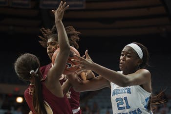 UNC freshman forward Malu Tshitenge (21) attempts to gain possession of the ball from Elon on Friday, Nov. 22, 2019 in Carmichael Arena. UNC won 76-46.