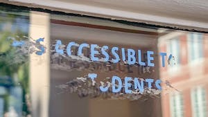 """DTH Photo Illustration. A sticker on the front door of Carroll Hall once read """"Is this accessible to all students?"""" but this message has been since scratched away."""