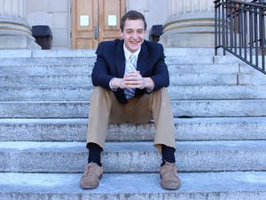 John Taylor sits on the steps of Wilson Library, one of his favorite places on campus. Taylor is currently running for student body president.