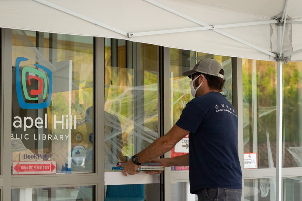 <p>Ryan Downs, 45, picks up books outside of the library on Oct. 21, 2020. The Chapel Hill Public Library has been awarded with a federal grant that funds computers, increased wifi coverage, and multilingual assistance throughout Chapel Hill.</p>