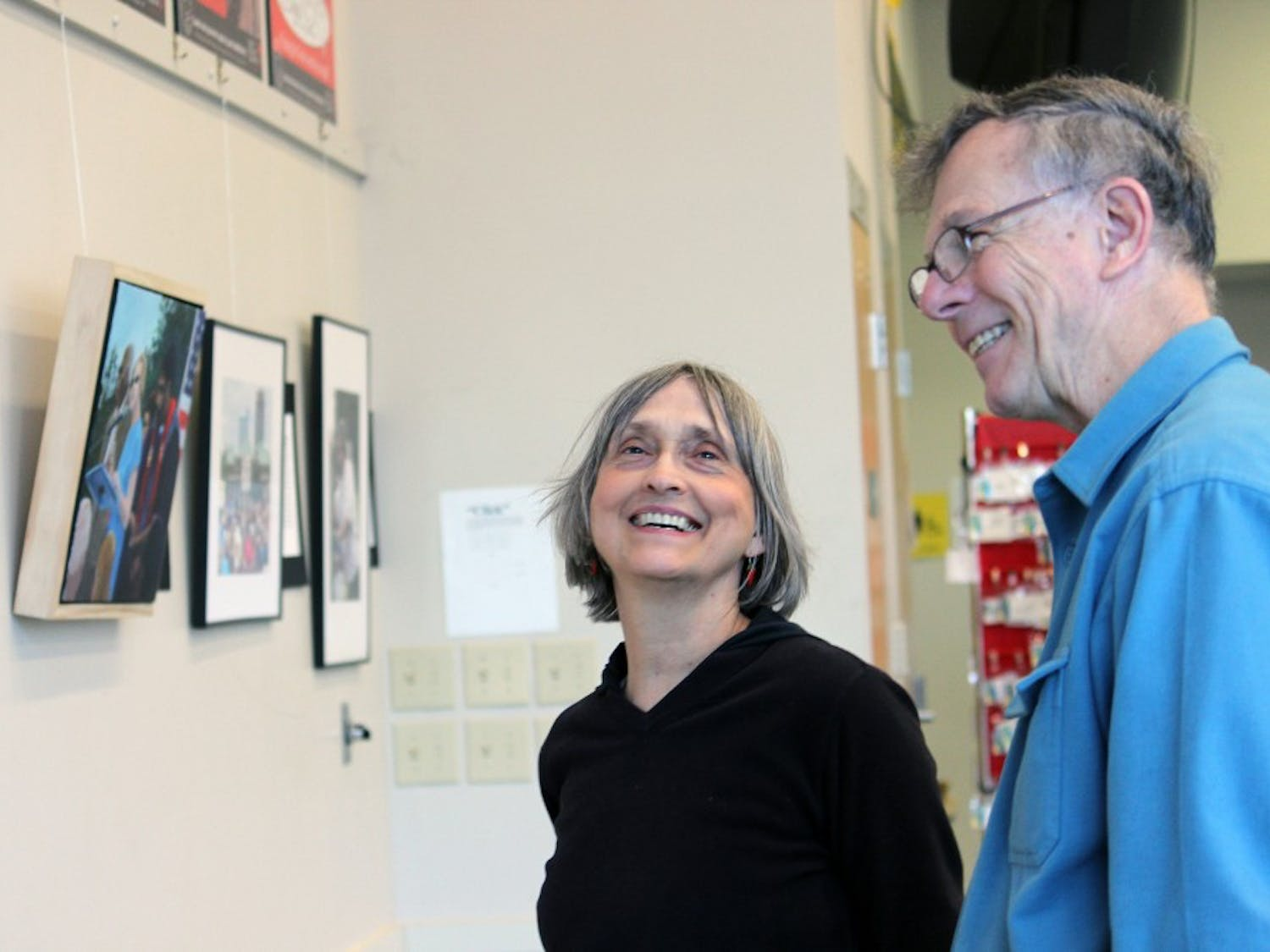"""Suzanne Lamport and one of the artists Dave Otto enjoy browsing the exhibition.  The activist exhibition of artist David Taylor, Harry Phillips, and photographer Dave Otto is called """"Images of Moral Mondays"""", which displays artwork of the ongoing speeches and protests of major issues, including unemployment, voting rights, health care, education, and many more."""