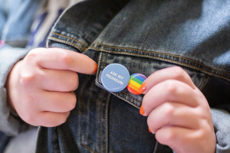 "DTH Photo Illustration. A student shows off the ""Ask my pronoun"" and pride flag buttons pinned to their jacket."