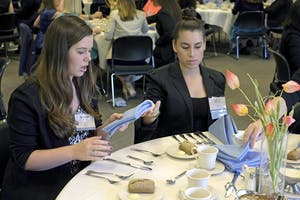 Seniors Brittney King (left) and Giselle Montgomery attempt to set their silverware as a part of the etiquette dinner Tuesday evening at the Friday Center.