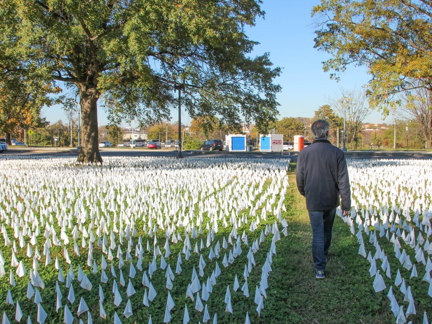 A visitor walks through the COVID-19 Flag Memorial in Washington, D.C. on Friday, Nov. 6, 2020. Every  flag honors an American death due to COVID-19.
