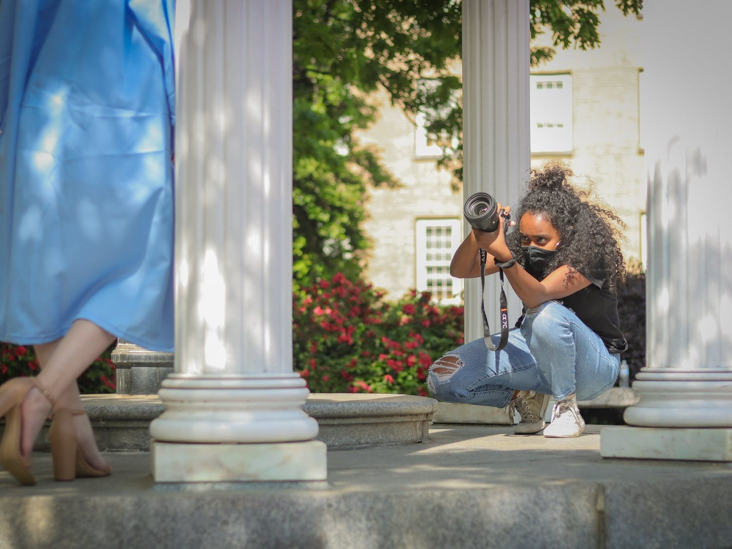 Hanna Wondmagegn, a UNC senior journalism major, takes graduation pictures of Deanna Upchurch, a senior peace, war and defense major at the Old Well.