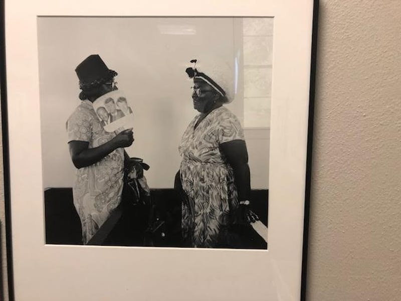 "A photo titled ""Women talking after church service at Hunter Chapel Missionary Baptist Church, 1971."" The photo is part of the exhibit of Cheryl Thurber photos being hosted by Wilson Library, detailing musical traditions in Gravel Springs, Mississippi."