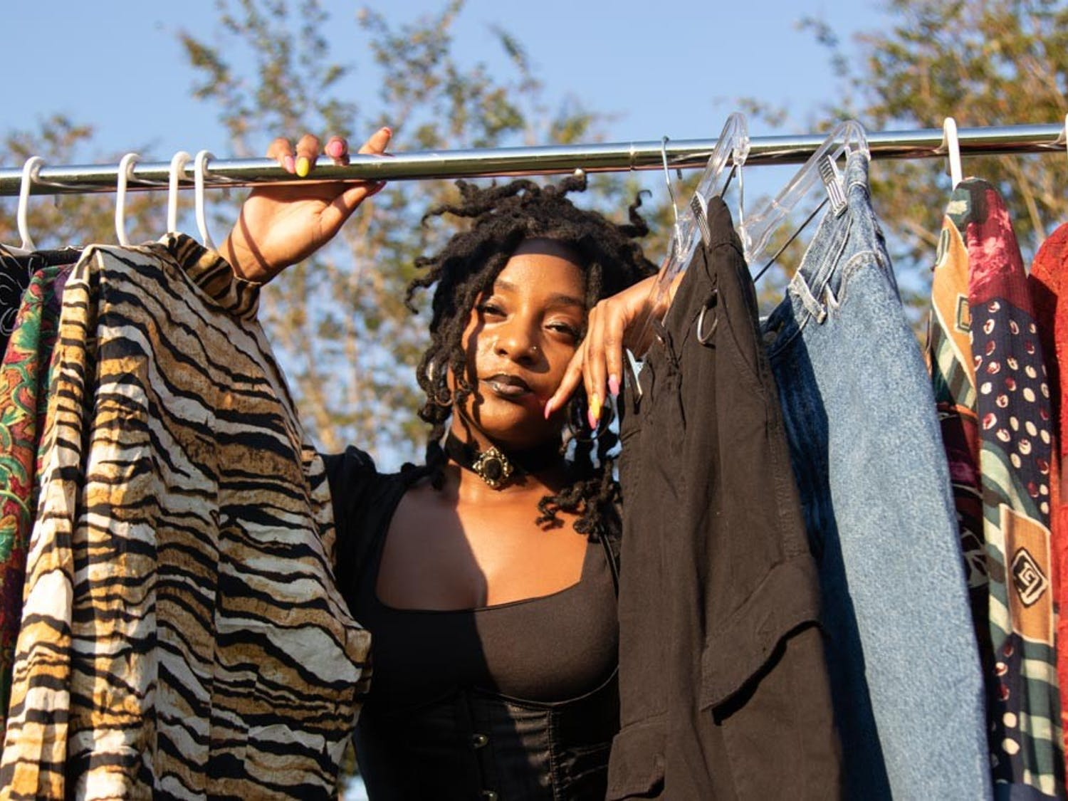 Alexandria Monet poses for a portrait with vintage clothing items she plans to sell for her business on Sept. 29. Monet owns She Thrifty Apparel where she sells curated vintage clothing apparel and aims to divert fashion waste.
