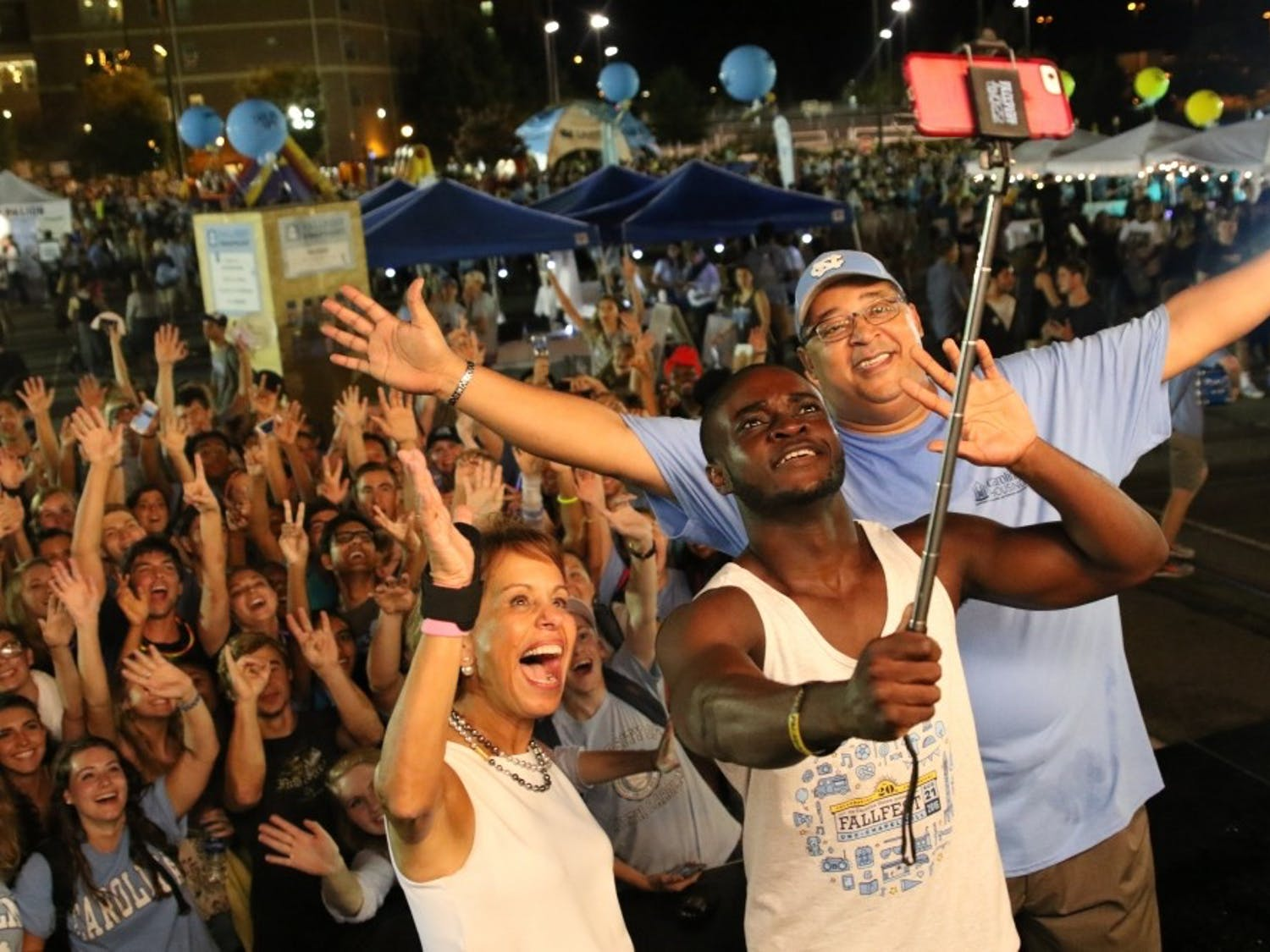 Chancellor Carol Folt (left), Boateng Kubi ,Chair of Carolina Union Board of Directors (center) and Vice Chancellor Winston Crisp (right) take a selfie with students at Fall Fest on Sunday, Aug. 21, 2016.