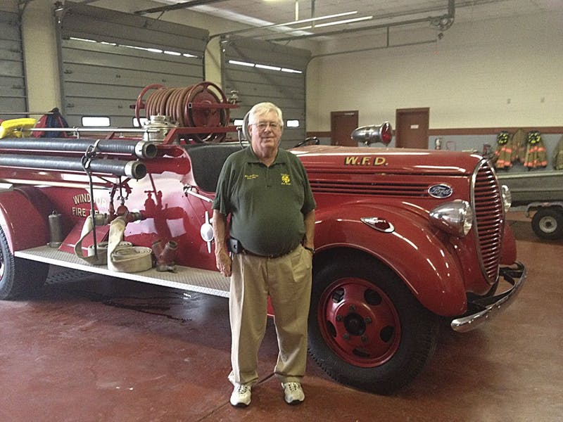 Chief Billy Smithwickstands in front of the fire station's first fire engine from1939.