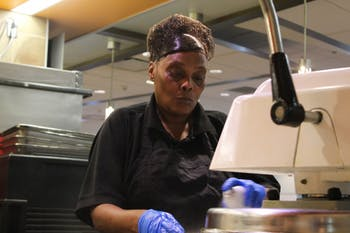 Angela Bynum, 55, of Chapel Hill making a pizza in Lenoir Dining Hall. Bynum has worked for Carolina Dining Services for about five years and enjoys talking to students in the dining hall.