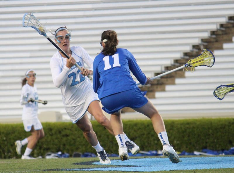 Women's lacrosse suffers a loss 7-6 to Duke in overtime on Wednesday in Kenan Stadium. Number 22 midfielder Maggie Bill dodges a Duke player during the first half.