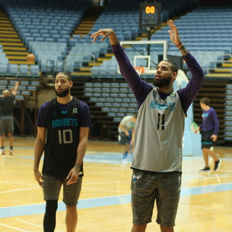 Charlotte Hornets forwards Caleb (10) and Cody Martin (11) competitively shoot around after training camp practice in the Dean E. Smith Center on Friday, Oct. 4, 2019.